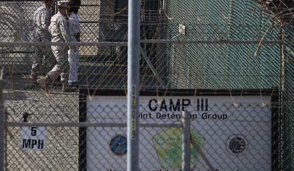 In this March 29, 2010 photo, reviewed by the U.S. military, a Guantanamo detainee is transported by guards inside the detention facility at Guantanamo Bay U.S. Naval Base, Cuba. The Obama Administration is pushing to close the Guantanamo detention facility, by  transferring, prosecuting, or releasing the remaining detainees. (AP Photo/Brennan Linsley)