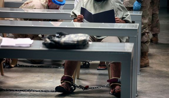 "In this photo, made through one way glass, reviewed by the U.S. military, a shackled Guantanamo detainee reads his materials as he attends a class in ""Life Skills,"" as guards in the background shackle another detainee to the floor after bringing him to the class, inside Camp 6 high-security detention facility at Guantanamo Bay U.S. Naval Base, Cuba, Tuesday, March 30, 2010. The Obama Administration is pushing to close the Guantanamo detention facility, by  transferring, prosecuting, or releasing the remaining detainees. (AP Photo/Brennan Linsley)"