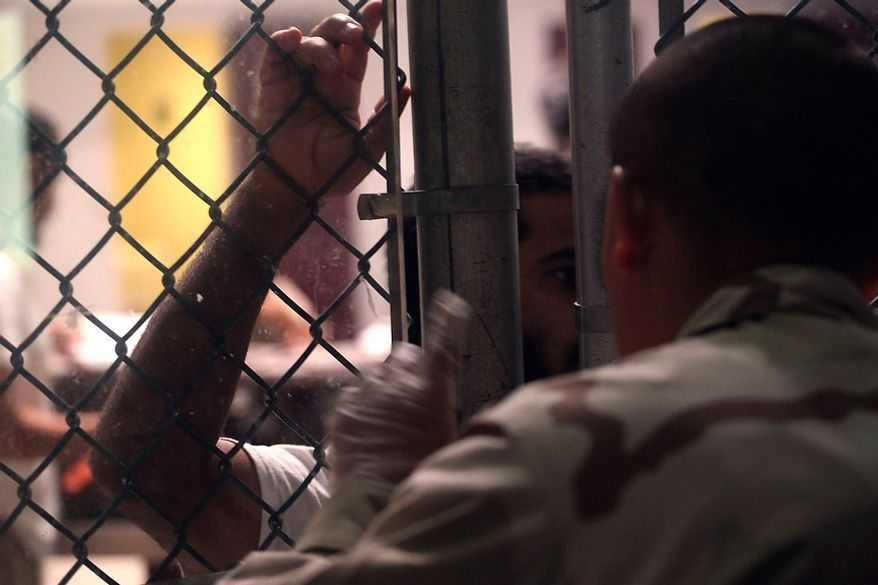In this March 30, 2010 photo, made through one way glass, reviewed by the U.S. military, a Guantanamo detainee talks with a guard through a fence inside Camp 6 high-security detention facility at Guantanamo Bay U.S. Naval Base, Cuba. The Obama Administration is pushing to close the Guantanamo detention facility, by  transferring, prosecuting, or releasing the remaining detainees. (AP Photo/Brennan Linsley)