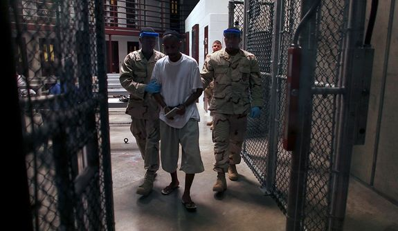 "In this March 30, 2010 photo, made through one way glass, reviewed by the U.S. military, a Guantanamo detainee carries a workbook as he is escorted by guards after the detainee attended a class in ""Life Skills,"" inside Camp 6 high-security detention facility at Guantanamo Bay U.S. Naval Base, Cuba. The Obama Administration is pushing to close the Guantanamo detention facility, by  transferring, prosecuting, or releasing the remaining detainees. (AP Photo/Brennan Linsley)"