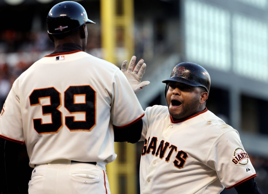 San Francisco Giants first base coach Roberto Kelly congratulates 3B Pablo Sandoval after Sandoval's RBI single against the St. Louis Cardinals during the second inning of Game 6 of the National League Championship Series on Oct. 21, 2012, in San Francisco. The Giants won 6-1 to force a decisive Game 7. (Associated Press)