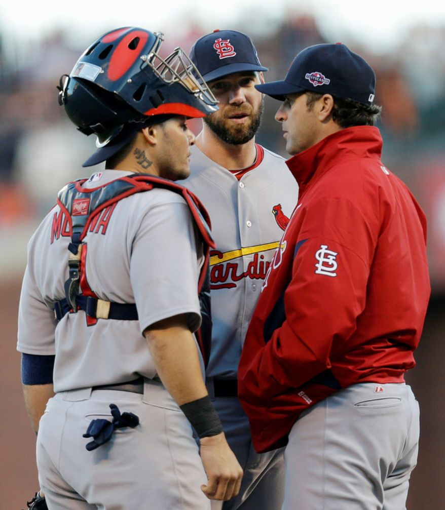 St. Louis Cardinals manager Mike Matheny (right) talks to starting pitcher Chris Carpenter (center) and catcher Yadier Molina during the second inning of Game 6 of the National League Championship Series against the San Francisco Giants on Oct. 21, 2012, in San Francisco. The Giants won 6-1 to force a decisive Game 7. (Associated Press)