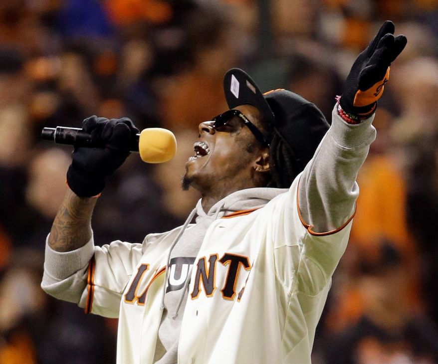 "Recording artist Lil Wayne sings ""Take Me Out To The Ball Game"" during the seventh inning of Game 6 of the National League Championship Series between the San Francisco Giants and the St. Louis Cardinals on Oct. 21, 2012, in San Francisco. The Giants won 6-1 to force a decisive Game 7. (Associated Press)"