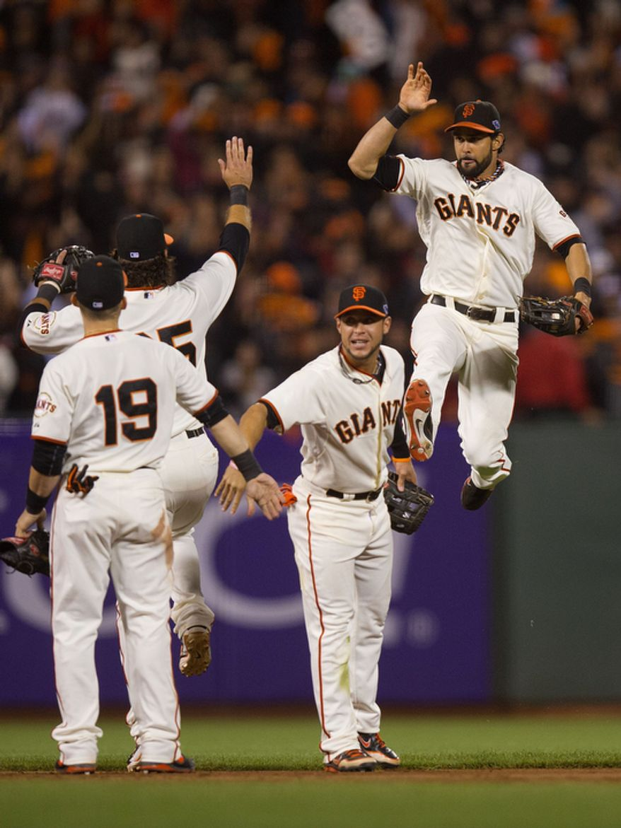 San Francisco Giants CF Angel Pagan (right) leaps into the air after the Giants' 6-1 victory over the St. Louis Cardinals in Game 6 of the National League Championship Series on Oct. 21, 2012, in San Francisco. The win forced a decisive Game 7. (Associated Press/The Sacramento Bee)
