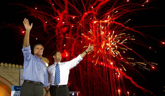 Republican presidential candidate, former Massachusetts Gov. Mitt Romney, left, and vice presidential running mate Rep. Paul Ryan, R-Wis., wave to the crowd as fireworks go off during a campaign rally on Friday, Oct. 19, 2012 in Daytona Beach, Fla.  (AP Photo/ Evan Vucci)