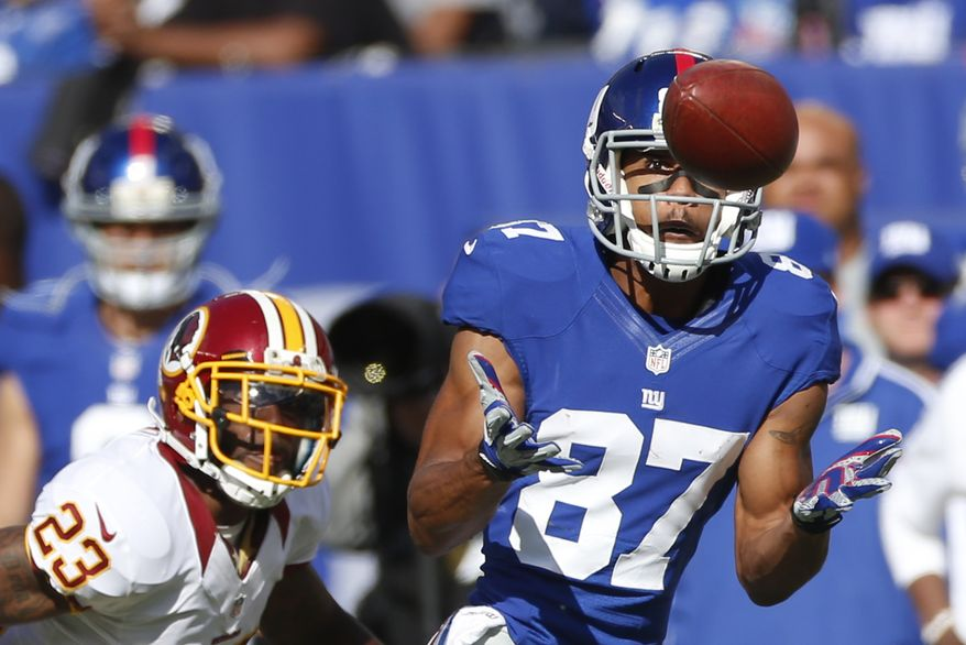 Washington Redskins cornerback DeAngelo Hall (23) New York Giants wide receiver Domenik Hixon (87) hauls in a pass during the first half of an NFL football game Sunday, Oct. 21, 2012 in East Rutherford, N.J. (AP Photo/Julio Cortez)