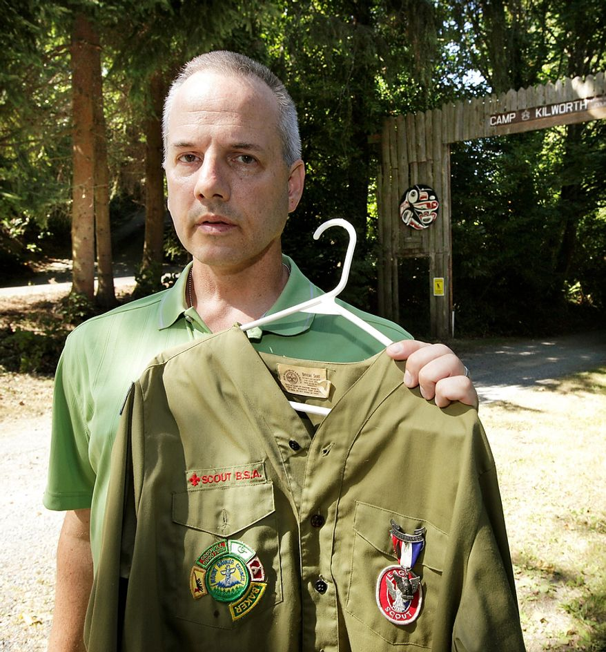"""Boy Scout abuse victim Tom Stewart poses Aug. 16, 2012, for a photo with his old Scout uniform outside the Boy Scout Camp Kilworth in Federal Way, Wash. Former Boy Scouts still struggle to cope with the abuse they suffered at the hands of Scout leaders, and those who are willing to tell the stories of their abuse have come to feel abandoned by an organization considered a pillar of American society. """"There are so many victims who have suffered in silence. Marriages and relationships with their kids have suffered,"""" said Stewart, a 46-year-old engineer for Boeing. (Associated Press)"""