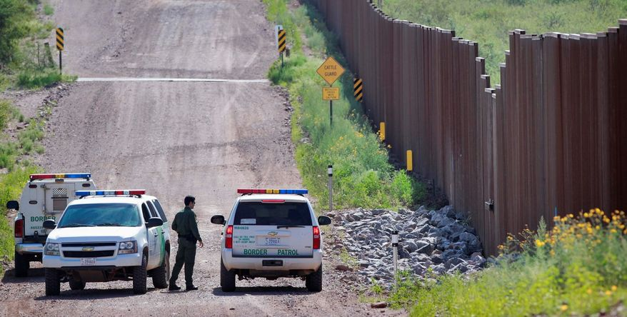 **FILE** U.S. Customs and Border Protection officers gather along the international border with Mexico near Naco, Ariz. (Associated Press)