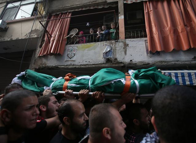 A Palestinian family (top) watches mourners Oct. 23, 2012, carry the body of Palestinian Ahmad Queider, 20, during a funeral procession in the Sunni neighborhood of Tarik al-Jadida in Beirut. The man was killed the day before as he rode his motorcycle during an exchange of gunfire between Lebanese troops and gunmen. (Associated Press)