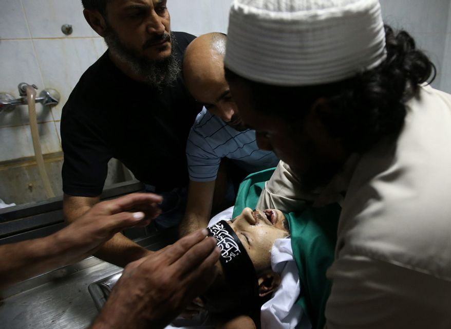 Mourners prepare the body of Palestinian Ahmad Queider, 20, for burial at a hospital morgue in the Sunni neighborhood of Tarik al-Jadida in Beirut on Oct. 23, 2012. Queider was killed Monday as he rode his motorcycle during an exchange of gunfire between Lebanese troops and gunmen. (Associated Press)
