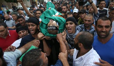 Mourners shout religious slogans Oct. 23, 2012, in the Sunni neighborhood of Tarik al-Jadida in Beirut during the funeral procession of Palestinian Ahmad Queider, 20, who was killed the day before as he rode his motorcycle during an exchange of gunfire between Lebanese troops and gunmen. (Associated Press)