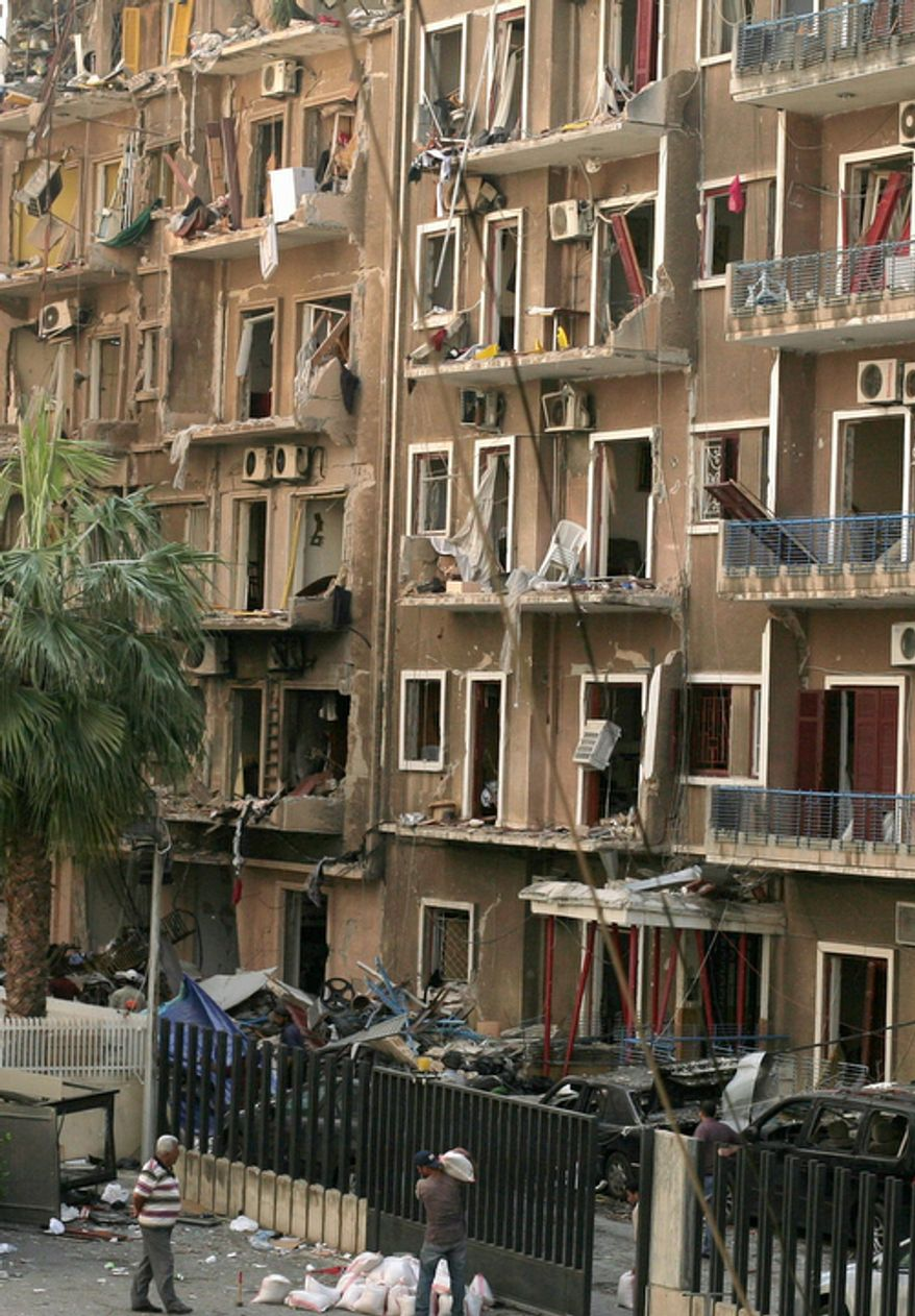 Workers stand near an apartment building severely damaged in a car bomb attack that killed Brig. Gen. Wissam al-Hassan in the Achrafieh district of Beirut on Oct. 23, 2012. (Associated Press)