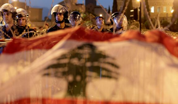 Lebanese riot police stand guard in front of the government palace behind a barbed wire barricade decorated with the national flag by anti-government protesters in downtown Beirut on Oct. 22, 2012. Lebanese troops launched a major security operation on Monday to open all roads and force gunmen off the streets, trying to contain an outburst of violence set off by the assassination of a top intelligence official who was a powerful opponent of Syria. Sectarian clashes killed at least five people. (Associated Press)