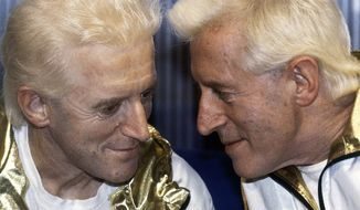 ** FILE ** TV host Jimmy Savile (right) poses for photographers with a wax model at Madame Tussauds museum in London in 1986. (AP Photo/John Redman)