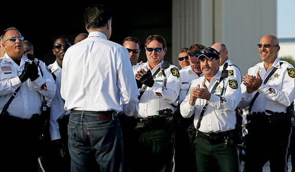 Police officers applaud as they are greeted by Republican presidential candidate Mitt Romney (with his back to the camera) before he boarded his campaign plane in West Palm Beach, Fla., on Tuesday, Oct. 23, 2012, en route to Nevada for a campaign stop, after last night's final presidential debate against President Obama. (AP Photo/David Goldman)