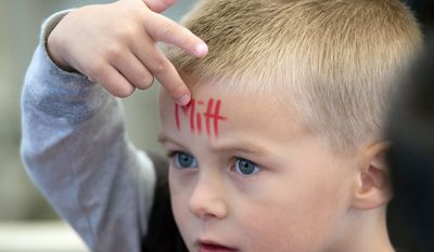 A young boy points to the name Mitt painted on his forehead while waiting for the arrival of Republican presidential candidate former Massachusetts Gov. Mitt Romney at a campaign rally, Tuesday, Oct. 23, 2012, at Henderson Pavilion in Henderson, Nev. (AP Photo/Julie Jacobson)