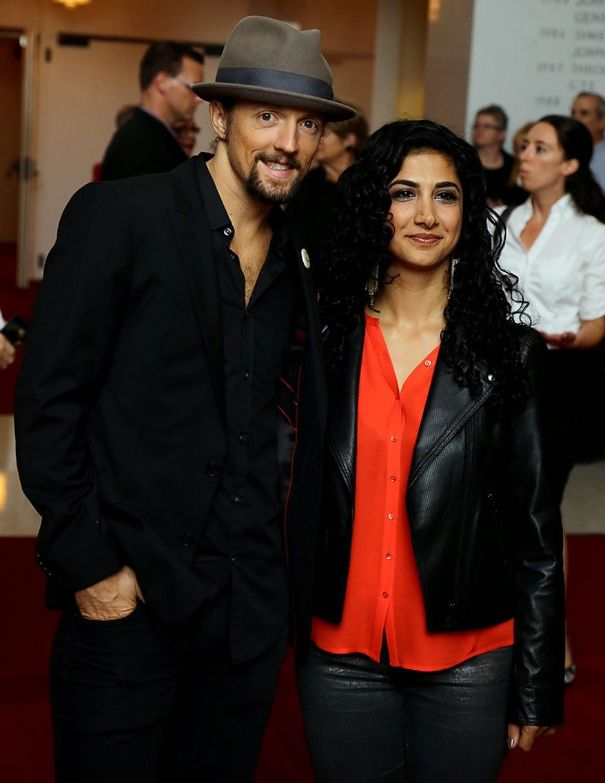 Musician Jason Mraz, left, with Mona Tavakoli pose for photographers on the red carpet before entertainer Ellen DeGeneres receives the 15th annual Mark Twain Prize for American Humor at the Kennedy Center, Monday, Oct. 22, 2012, in Washington. (AP Photo/Alex Brandon)