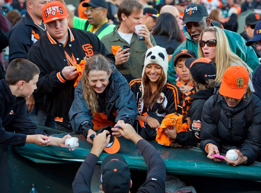 San Francisco Giants front office member Will Clark signs autographs for fans before Game 7 of the National League Championship Series between the Giants and the St. Louis Cardinals on Oct. 22, 2012, in San Francisco. (Associated Press/The Sacramento Bee)