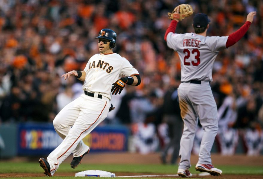 San Francisco Giants 2B Marco Scutaro rounds third base as St. Louis Cardinals 3B David Freese (23) calls for the throw during the third inning of Game 7 of the National League Championship Series on Oct. 22, 2012, in San Francisco. (Associated Press/The Sacramento Bee)