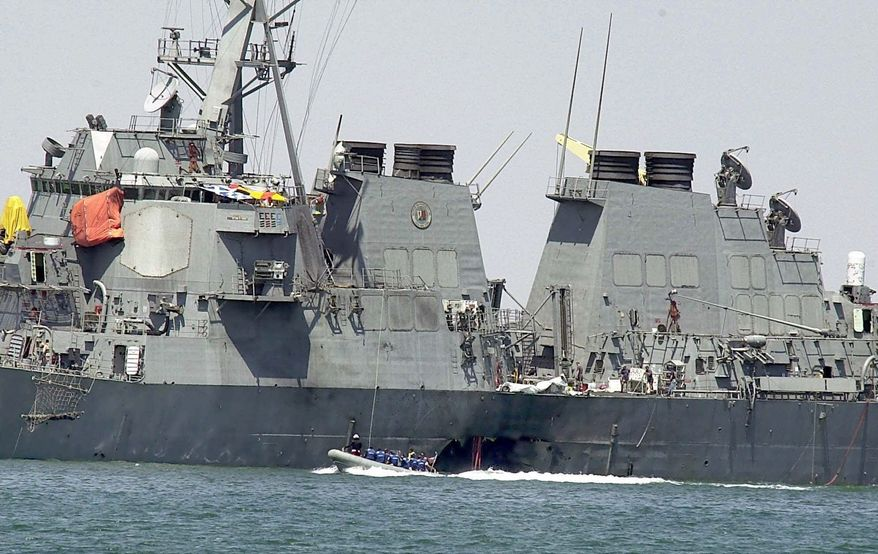 Investigators in a speed boat examine the hull of the USS Cole at the Yemeni port of Aden on Oct. 15, 2000, after a powerful explosion ripped a hole in the U.S. Navy destroyer, killing at least 17 sailors and injuring some 30 others. (AP Photo/Dimitri Messinis)