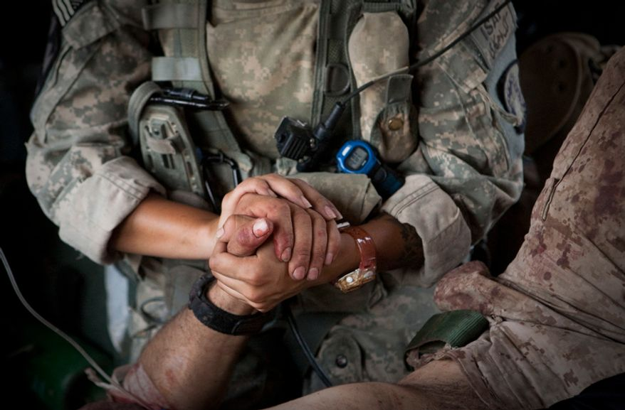 ** FILE ** U.S. Army chief Spc. Jenny Martinez holds the hand of an injured U.S. Marine who was wounded in an IED strike in June, 2011. (AP Photo/Anja Niedringhaus)