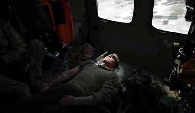 """In this picture taken Sunday, May 8, 2011, US Marine Staff Sgt. Tony Palomo of Louisiana is flown to hospital on a  medevac helicopter from the US Army's Task Force Lift """"Dust Off"""", Charlie Company 1-214 Aviation Regiment north of Forward Operating Base Edi, after being injured in an IED blast in the volatile Helmand Province of southern Afghanistan. (AP Photo/Kevin Frayer)"""