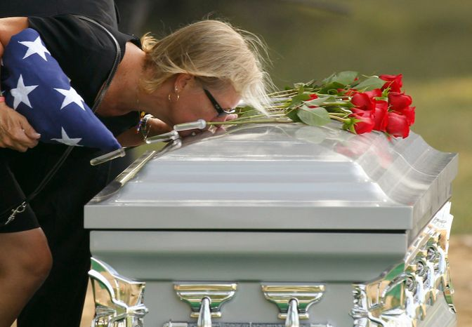 Tammy O'Brien kisses the casket one last time after services for her son Marine Lance Corporal Nicholas O'Brien, Tuesday, June 28, 2011, at Arlington National Cemetery  in Arlington, Va. O'Brien died June 9 from an IED (improvised explosive device) in Helmand province in southern Afghanistan. (AP Photo/Alex Brandon)