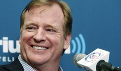 NFL Commissioner Roger Goodell smiles as he talks with former New York Giants defensive end Michael Strahan, not shown, and football fans during a Sirius XM Town Hall event in New York, Monday, Oct. 22, 2012. (AP Photo/Seth Wenig)