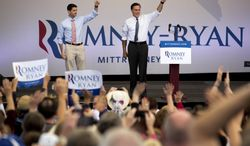 Republican presidential candidate Mitt Romney (right) and his running mate, Paul Ryan, greet supporters Oct. 23, 2012, before a rally in Las Vegas. (Associated Press)