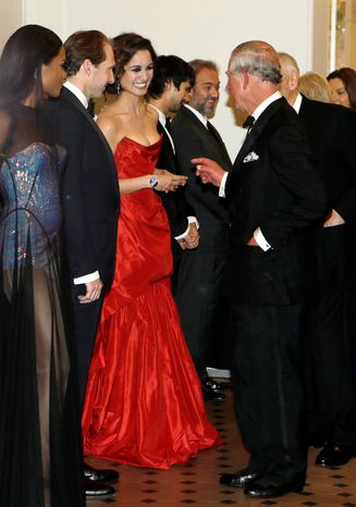 """Britain's Prince of Wales, right, meets Bond girl Berenice Marlohe as he arrives to attend the world premiere of the James Bond film, """"Skyfall"""", at the Royal Albert Hall, in London Tuesday, Oct. 23, 2012. (AP Photo/Kirsty Wigglesworth, Pool)"""