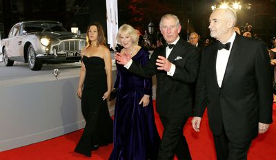 """Britain's Prince of Wales, second right, and The Duchess of Cornwall, second left, are escorted by the film producers Michael G. Wilson, right, and Barbara Broccoli, left, as they arrive to attend the world premiere of the James Bond film, """"Skyfall"""", at the Royal Albert Hall, in London Tuesday, Oct. 23, 2012. (AP Photo/Kirsty Wigglesworth, Pool)"""