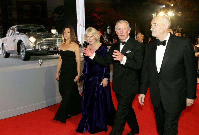 "Britain's Prince of Wales, second right, and The Duchess of Cornwall, second left, are escorted by the film producers Michael G. Wilson, right, and Barbara Broccoli, left, as they arrive to attend the world premiere of the James Bond film, ""Skyfall"", at the Royal Albert Hall, in London Tuesday, Oct. 23, 2012. (AP Photo/Kirsty Wigglesworth, Pool)"