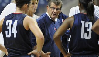 Connecticut coach Geno Auriemma speaks with Kelly Faris (34) as Brianna Banks (13) listens during practice before the NCAA college basketball team's media day in Storrs, Conn., Tuesday, Oct. 16, 2012. (AP Photo/Jessica Hill)