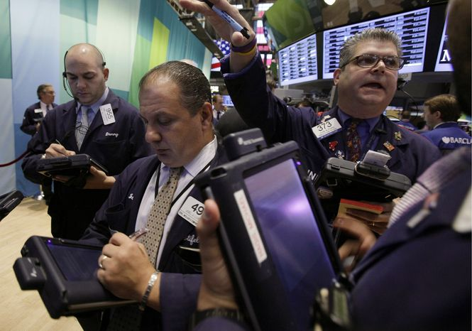 Trader John Panin (right) works Oct. 23, 2012, on the floor of the New York Stock Exchange. (Associated Press)