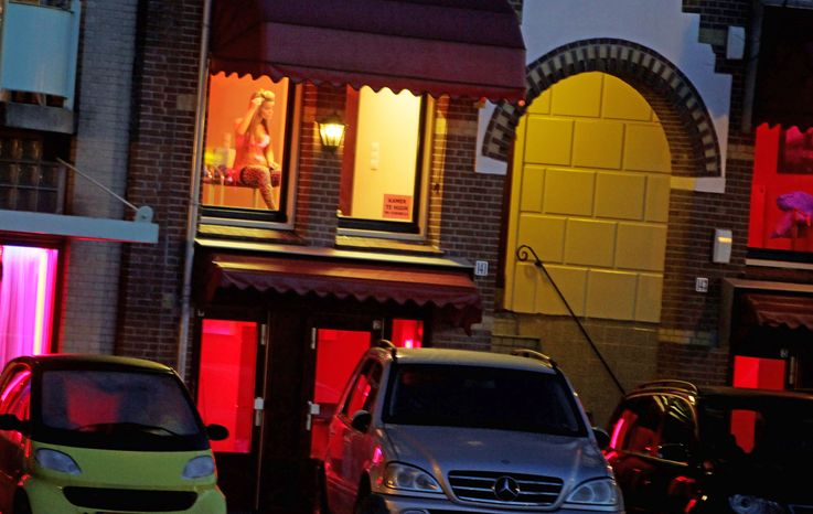 ** FILE ** A prostitute advertises in a window in Amsterdam's Red Light District. (Associated Press)