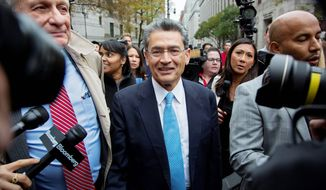 Rajat Gupta (center) leaves federal court in New York on Wednesday after the former Goldman Sachs board member was sentenced to two years in prison for feeding inside information to his friend. (Associated Press)