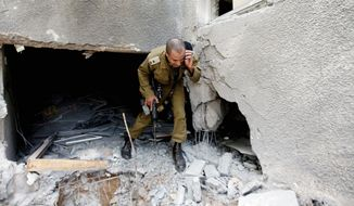 An Israeli military officer surveys the damage of a house after a rocket fired by Palestinian militants hit a community along the Israel-Gaza border in Israel on Wednesday. Rockets and mortars from Gaza have pummeled southern Israel. (The Associated Press)