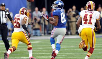 Wide receiver Victor Cruz prepares to gather in a 77-yard touchdown pass as Redskins defensive backs Josh Wilson and Madieu Williams pursue him. (Associated Press)