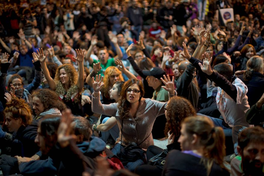 Demonstrators shout slogans against the government Oct. 23, 2012, in Madrid outside Parliament as lawmakers debate budget spending cuts for 2013. (Associated Press)