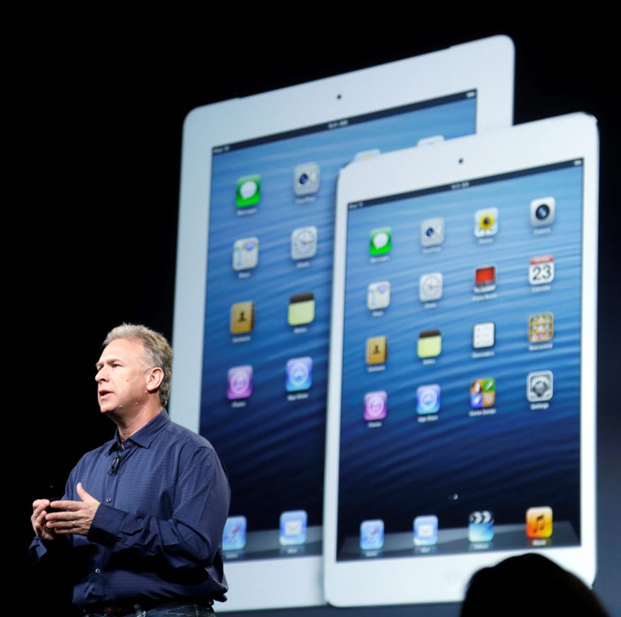 Phil Schiller, Apple's senior vice president of worldwide product marketing, speaks in front of an image of the fourth-generation iPad (left) and the iPad Mini in San Jose, Calif., on Tuesday, Oct.  23, 2012. The Mini has a screen that's about two-thirds the size of the full-size model, and Apple says it will cost $329 and up.  (AP Photo/Marcio Jose Sanchez)