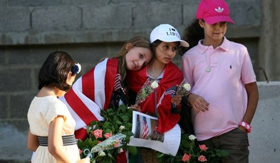 Libyan and American children carry a wreath Sept. 17, 2012, with a photo of U.S. Ambassador Chris Stevens on it as they gather in Benghazi, Libya, to pay their respect to the victims of the Sept. 11 attack on the U.S. consulate. Stevens and three other Americans were killed in the attack. (Associated Press)