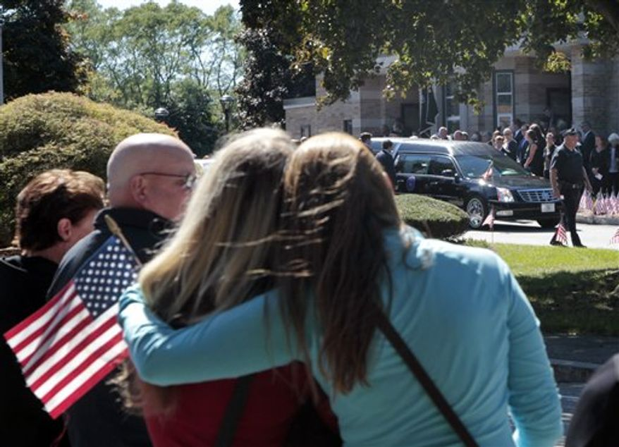 **FILE** Two women hold each other Sept. 19, 2012, as they watch the hearse of former Navy SEAL Glen Doherty leave the Church of St. Eulalia in Winchester, Mass., after his funeral. Doherty, 42, and three others, including the U.S. ambassador to Libya, died in a Sept. 11 attack on the U.S. consulate in Libya. (Associated Press)