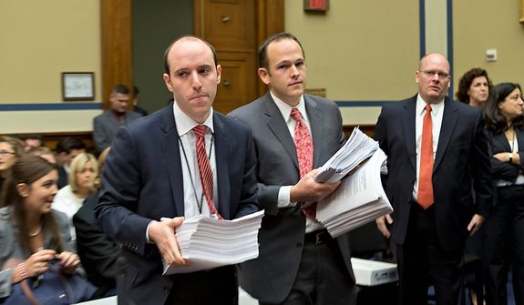 **FILE** Aides bearing armfuls of papers arrive Oct. 10, 2012, on Capitol Hill with witnesses from the State Department for the House Oversight and Government Reform Committee hearing investigating the Sept. 11 attack on the American consulate in Benghazi, Libya, that resulted in the death of U.S. Ambassador Christopher Stevens and other Americans. (Associated Press)