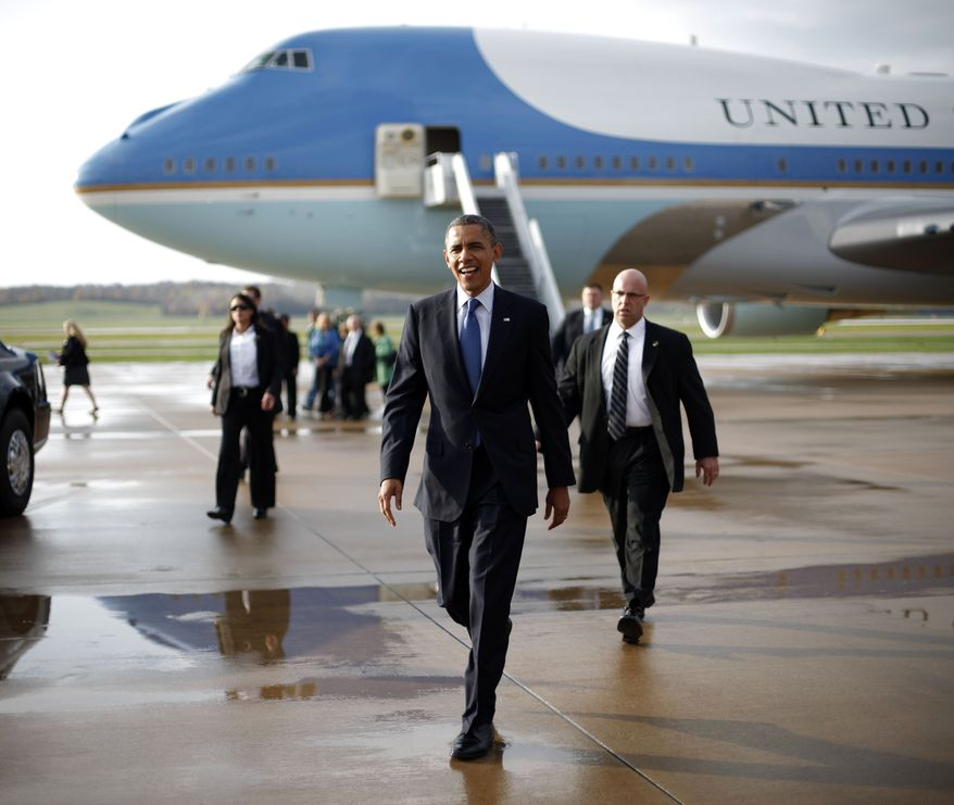 President Obama walks Oct. 24, 2012, across the tarmac to greet supporters upon his arrival on Air Force One at the Quad Cities International Airport in Moline, Ill., as the president began a two-day campaign blitz, through eight states with stops in key battleground areas of Iowa, Colorado, Nevada, Ohio and Virginia. (Associated Press)