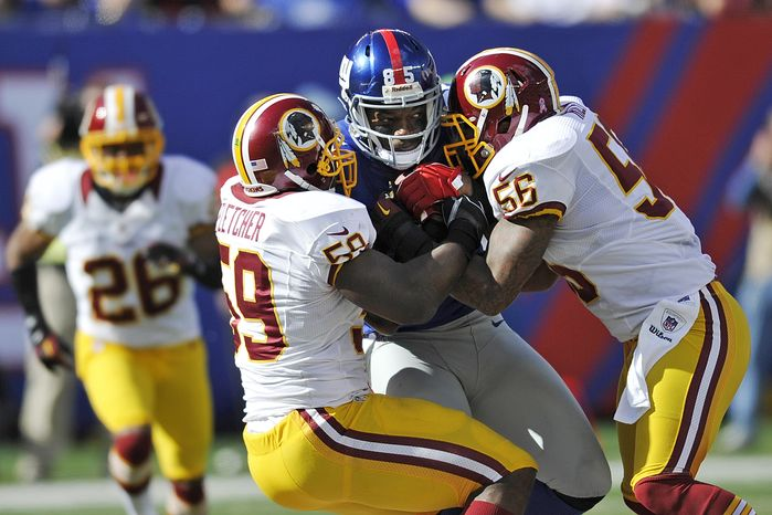 New York Giants tight end Martellus Bennett (85) is tackled by Washington Redskins inside linebacker Perry Riley (56) as London Fletcher (59) closes in during the first half of an NFL football game Sunday, Oct. 21, 2012 in East Rutherford, N.J. (AP Photo/Bill Kostroun)