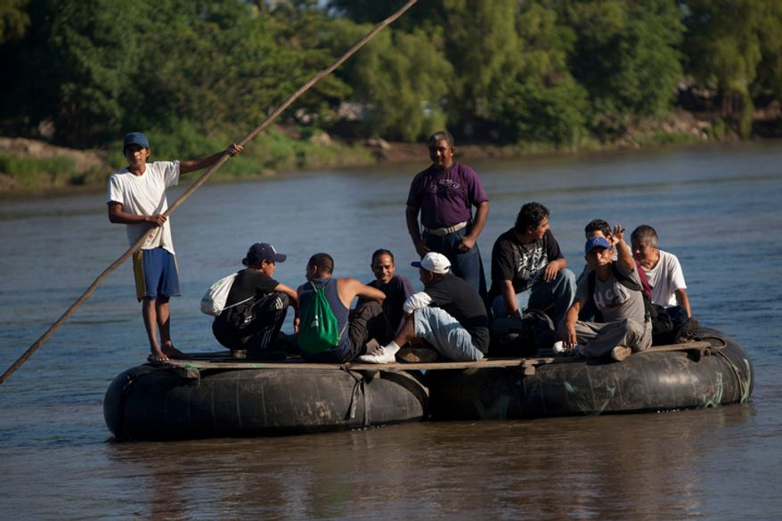 **FILE** A Guatemalan river-raft worker steers a group of Central American migrants journeying north to the U.S., across the Suchiate river on a makeshift raft at the Guatemala-Mexico border crossing in Tecun Uman, Guatemala, on Sept. 28, 2012. (Associated Press)