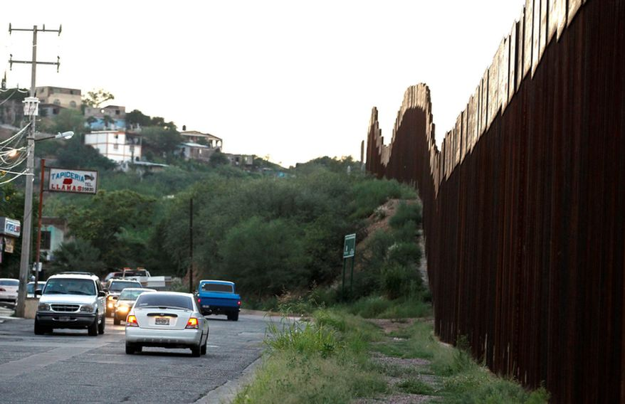 **FILE** Vehicles drive Aug. 9, 2012, along the border fence in Nogales, Mexico. (Associated Press)