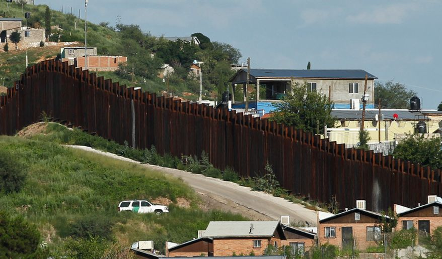 **FILE** A U.S. Border Patrol vehicle keeps watch Aug. 9, 2012, along the border fence in Nogales, Ariz. (Associated Press)