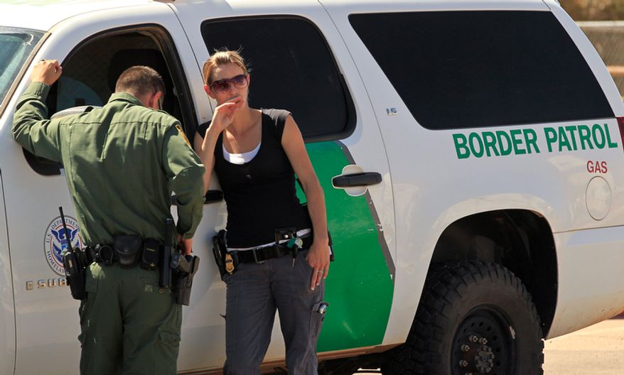 **FILE** Hours after a U.S. Border Patrol agents were shot, killing one, agents stand Oct. 2, 2012, beside an agency vehicle in front of the U.S. Customs and Border Protection Brian A. Terry Border Patrol Station in Bisbee, Ariz. (Associated Press)