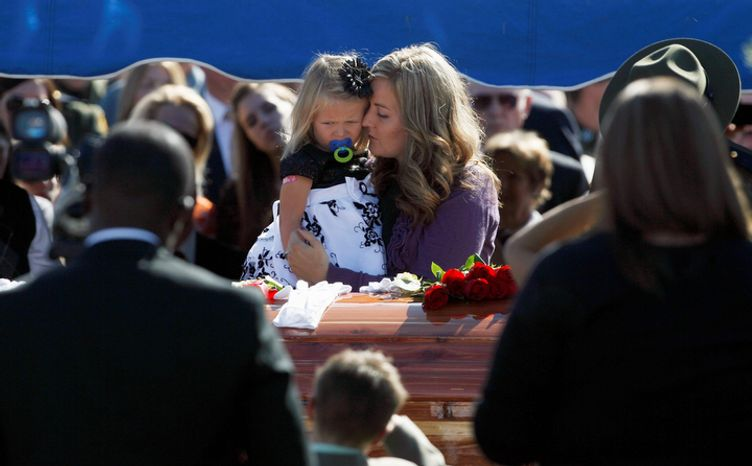 Christy Ivie holds her daughter, Raigan, 3, as she stands by the casket of her husband, Border Patrol Agent Nicholas Ivie, during funeral services at Spanish Fork City Cemetery in Spanish Fork, Utah, on Oct. 11, 2012. Ivie, a Provo, Utah, native, was killed Oct. 2 in a shooting at the Arizona-Mexico border. (Associated Press/The Salt Lake Tribune)